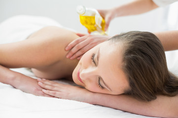 Beautiful woman enjoying oil massage at beauty spa
