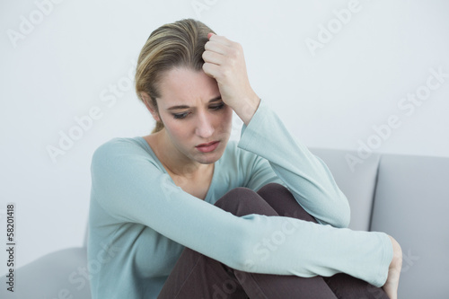 Troubled casual woman sitting on couch