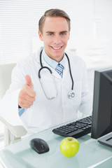 Doctor using computer while gesturing thumbs up at medical offic