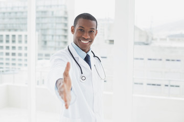 Smiling doctor offering a handshake in a medical office