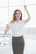 Elegant businesswoman cheering in office