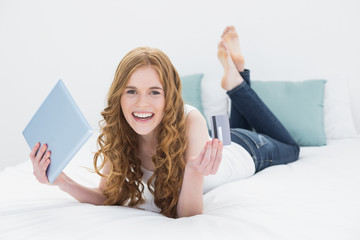Cheerful blond holding tablet PC and credit card in bed