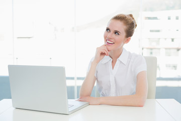 Thoughtful businesswoman using laptop at office desk