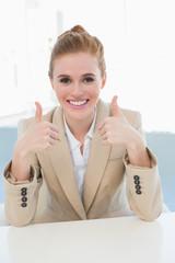 Elegant businesswoman gesturing thumbs up