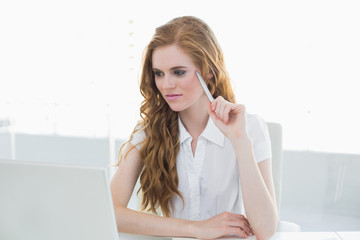 Beautiful young businesswoman looking at laptop