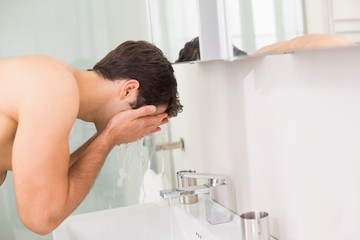 Shirtless young man washing face in bathroom