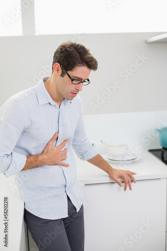 Casual man with stomach pain standing in the kitchen