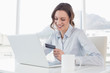 Smiling businesswoman doing online shopping in office