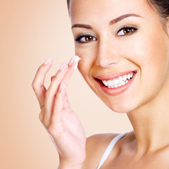 Smiling woman applying cosmetic cream
