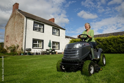 Senior lady cutting lawn of country farm house