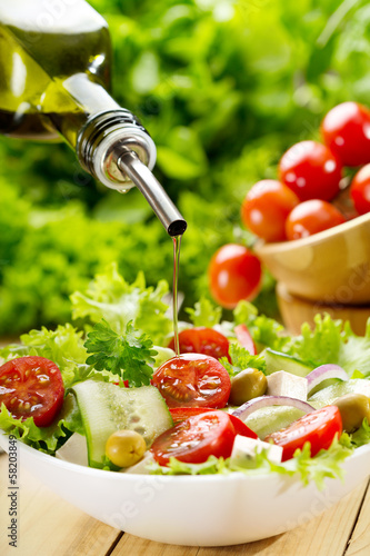 olive oil pouring over salad