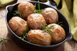baked potatoes with rosemary in black pan