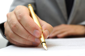 businessman is fulfilling and signing contract with fountain pen