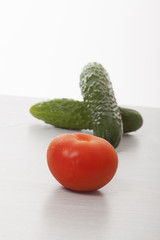 red tomato and cucumber on white table