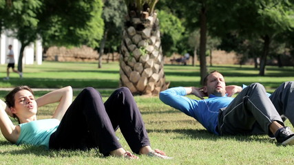Young couple doing sit-ups on the grass in the park