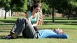 Young man doing crunches in park with help of personal trainer