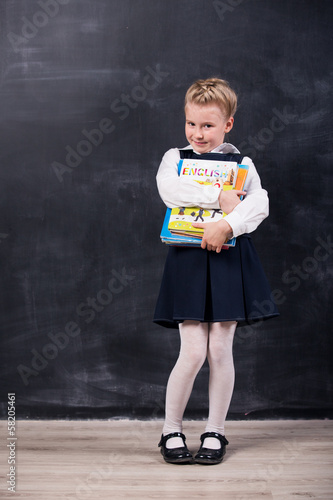 Schoolgirl with books  near blackboard