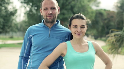 Happy young joggers couple standing in the park