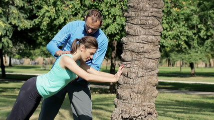 Young woman stretching and bending by the tree with the trainer