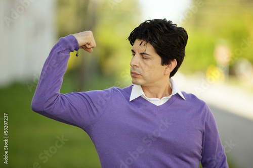 Weak man flexing his muscles