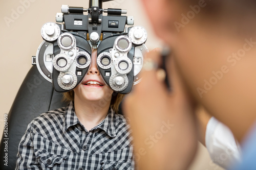 Boy Undergoing Eye Test With Phoropter