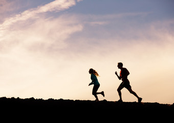 Silhouette of man and woman running jogging together into sunset