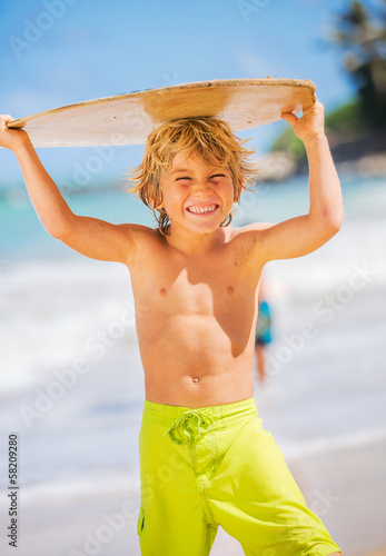 Happy Young boy having fun at the beach on vacation, with skimbo