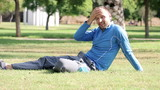 Happy young man resting on grass in park after sport