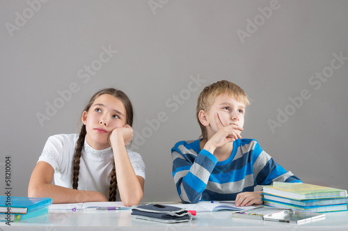 Bored children sitting by the table and looking away