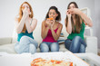 Happy young female friends eating pizza at home