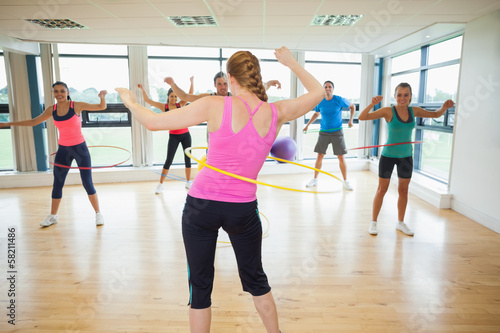Fitness class and instructor swinging hula hoops at the waist