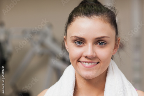 Smiling woman with towel around neck in gym