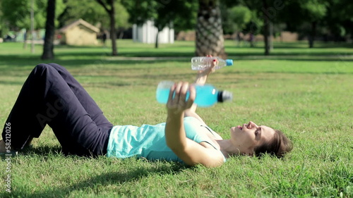 Young woman doing biceps exercise using bottles as a weights