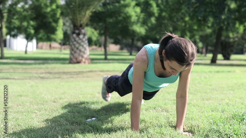 Young sportswoman exercising plank on a grass in the park