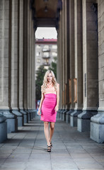 blond fashion woman walking between columns