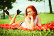 beautiful woman with red hair has rest in park