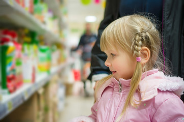 Adorable girl in pink select products on shelves in supermarket