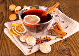 Mulled wine in glass with cinnamon stick, gingerbread and nuts