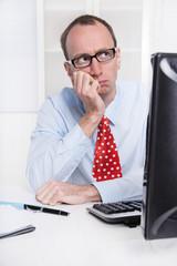 Mann nachdenklich und skeptisch sitzend im Büro