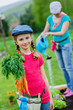Gardening - girl with mother working in the garden