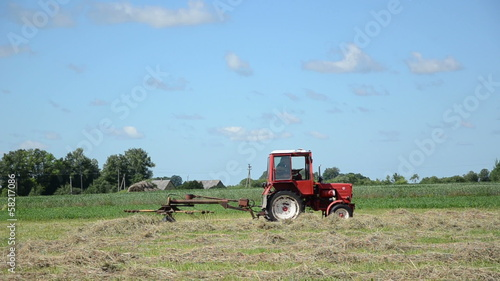 Panorama of tractor ted hay dry grass in agriculture field