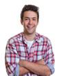 Lachender junger Mann mit verschränkten Armen und kariertem Hemd
