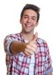 Lachender junger Mann im karierten Hemd zeigt den Daumen hoch