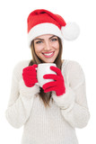 Cute happy Santa girl drinking hot beverage