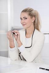Frau feilt sich die Fingernägel im Büro - Blondine