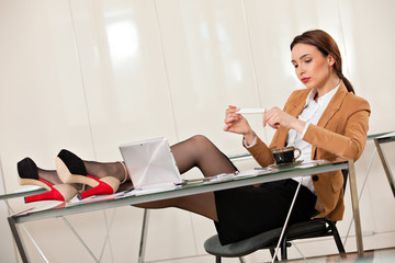business woman holding legs on the desk