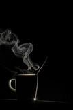 Taza de café caliente en silueta sobre fondo negro