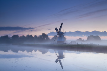 Dutch windmill reflected in river in sunrise fog