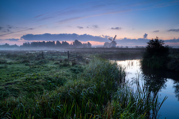 misty morning over Dutch farmland with windmill and river