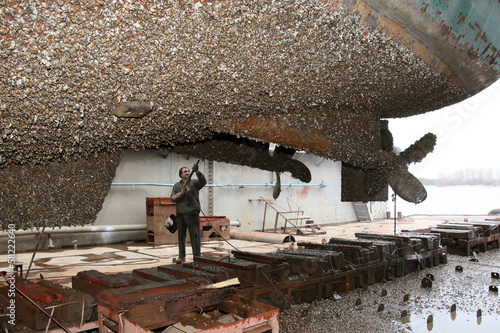 Shipyard worker cleans the ship stuya water